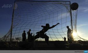 Afghan youth play soccer on the outskirts of Herat on January 17, 2014